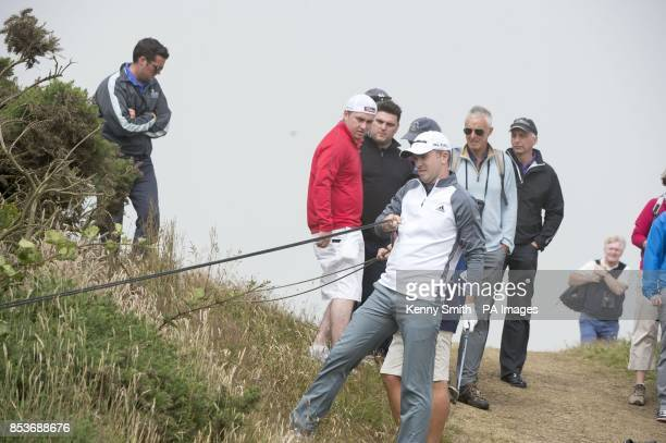 Scotland's Martin Laird has to move TV cables in order to play his shot from the deep rough during day three of the Aberdeen Asset Management...