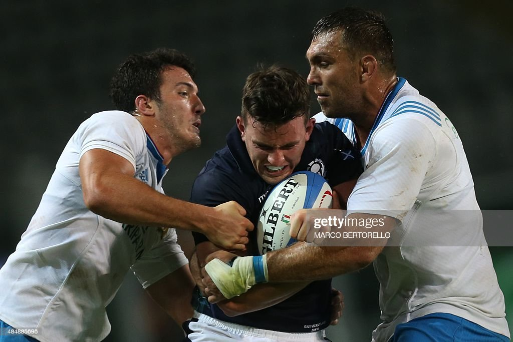 Scotland's <a gi-track='captionPersonalityLinkClicked' href=/galleries/search?phrase=Matt+Scott+-+Rugby+Union+Player&family=editorial&specificpeople=15066775 ng-click='$event.stopPropagation()'>Matt Scott</a> is tackled by Italy's Quintin Geldenhuys (R) and Italy's Giovanbattista Venditti during the Rugby World Cup Test match Italy Vs Scotland on August 22, 2015 at the 'Olympic Stadium' in Turin.