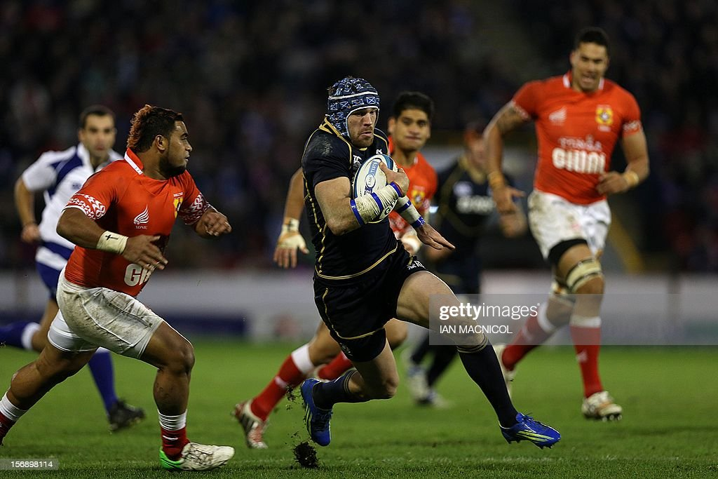 Scotland's Sean Lamont (C) runs through the Tonga defence during the International rugby union test match between Scotland and Tonga at Pittodrie in Aberdeen on November 24, 2012. Tonga beat Scotland 21-15.