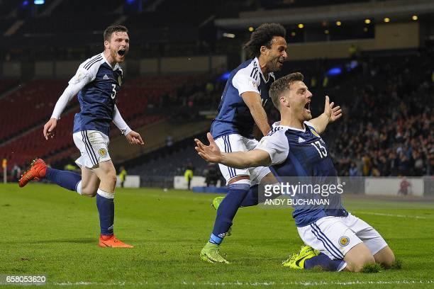 Scotland's striker Chris Martin celebrates scoring the only goal with Scotland's defender Andrew Robertson and Scotland's defender Ikechi Anya during...
