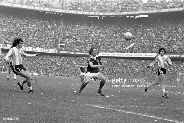 Scotland's Willie Johnston chases a through ball watched by Argentina's Rene Houseman and Daniel Passarella