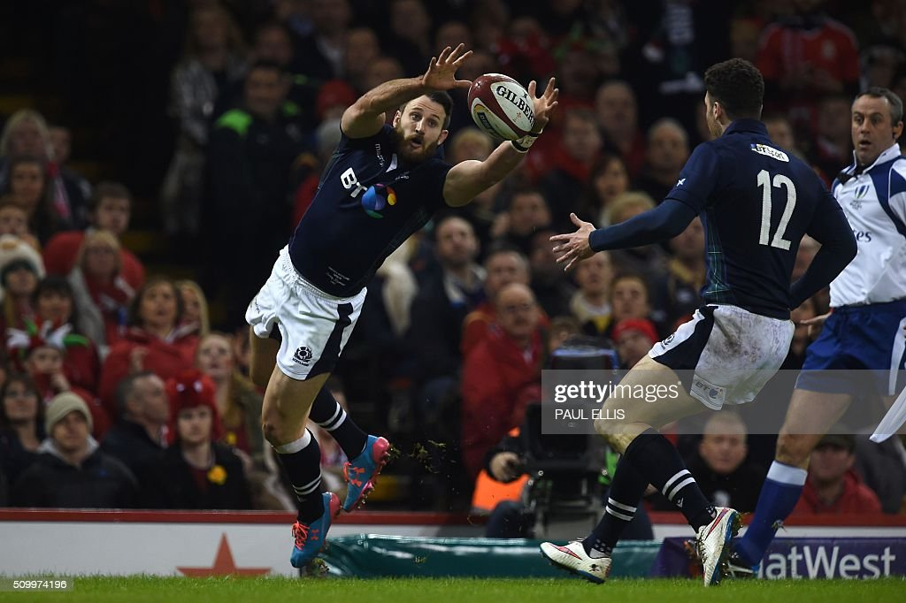 Scotland's wing Tommy Seymour (L) catches the ball to score his team's first try during the Six Nations international rugby union match between Wales and Scotland at the Principality Stadium in Cardiff, south Wales, on February 13, 2016. / AFP / PAUL ELLIS / RESTRICTED TO EDITORIAL USE. Use in books subject to Welsh Rugby Union (WRU) approval.