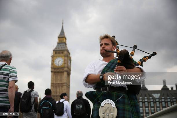 Scotsman David Whitney plays the bagpipes on Westminster Bridge in sight of Parliament on September 10 2014 in London England English councils and...