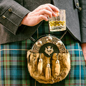 Close-up of a man wearing a kilt and sporran, holding a dram of Scotch whisky.