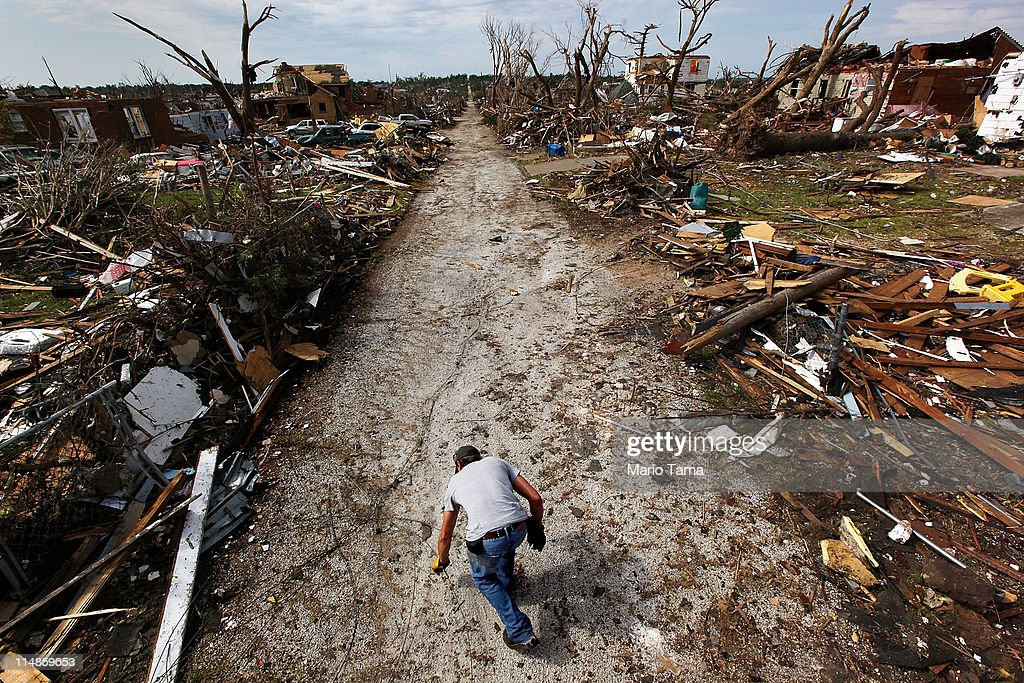 Scott Anderson reaches for a piece of debris near his heavily damaged home after a massive tornado passed through the town killing at least 132 people on May 27, 2011 in Joplin, Missouri. Anderson said, 'It's like they dropped a bomb on us.' The town continues the process of recovering from the storm which damaged or destroyed an estimated 8,000 structures.