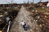 Scott Anderson reaches for a piece of debris near his heavily damaged home after a massive tornado passed through the town killing at least 132...