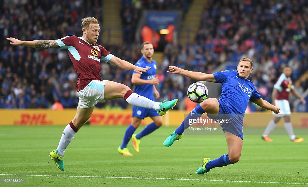 Scott Arfield of Burnley (L) and Daniel Drinkwater of Leicester CiDaniel Drinkwater of Leicester City(R) both stretch to reach to the ball during the Premier League match between Leicester City and Burnley at The King Power Stadium on September 17, 2016 in Leicester, England.