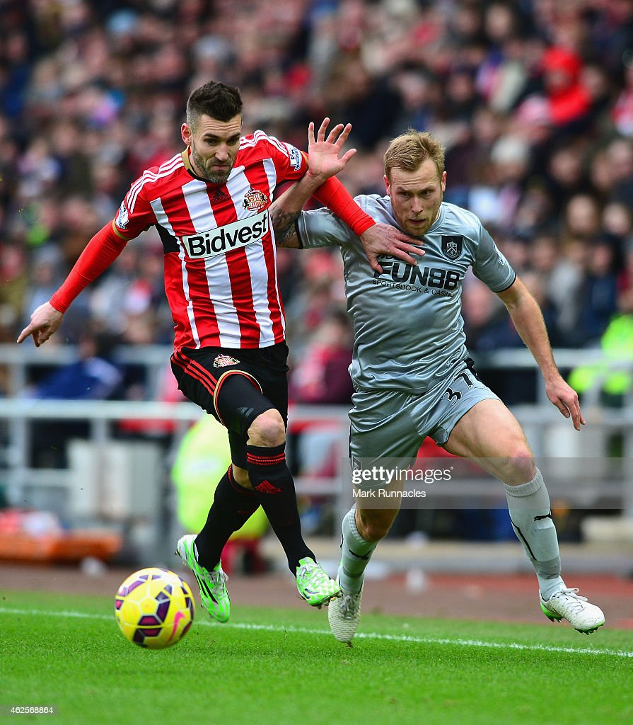 Scott Arfield of Burnley battles with Anthony Reveillere of Sunderland during the Barclays Premier League match between Sunderland and Burnley at Stadium of Light on January 31, 2015 in Sunderland, England.