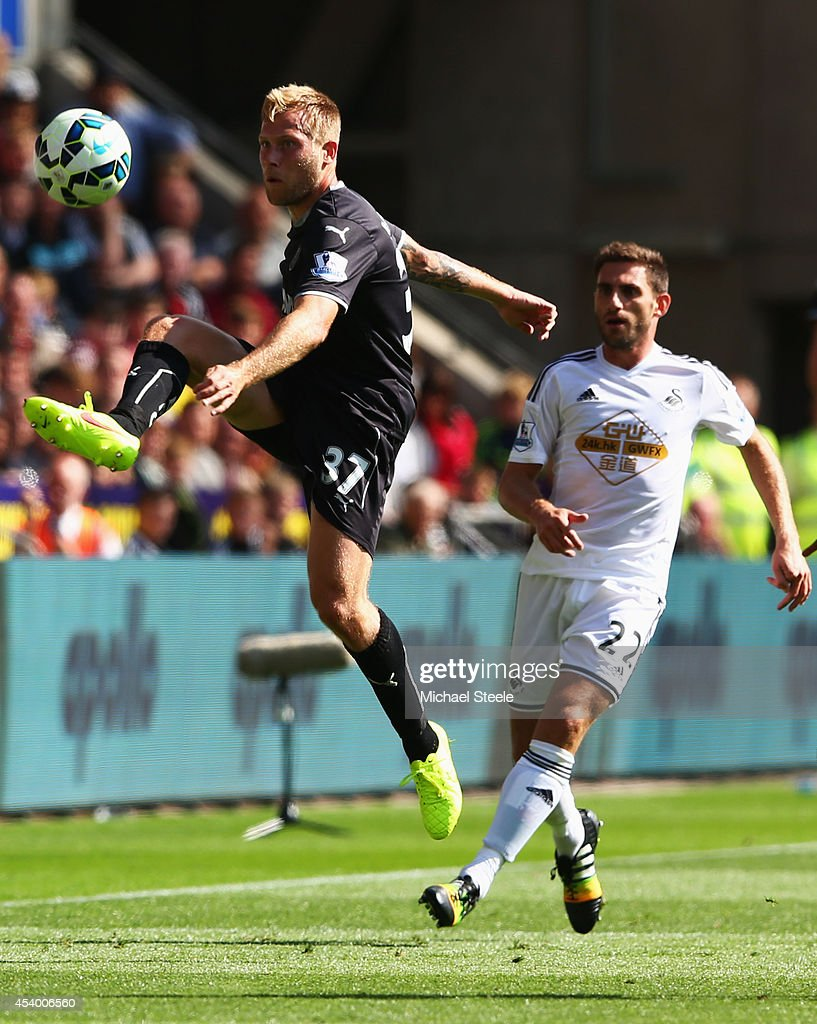 Scott Arfield of Burnley beats Angel Rangel of Swansea City to the ball during the Barclays Premier League match between Swansea City and Burnley at Liberty Stadium on August 23, 2014 in Swansea, Wales.