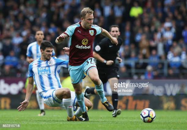 Scott Arfield of Burnley runs past Christopher Schindler of Huddersfield Town during the Premier League match between Burnley and Huddersfield Town...