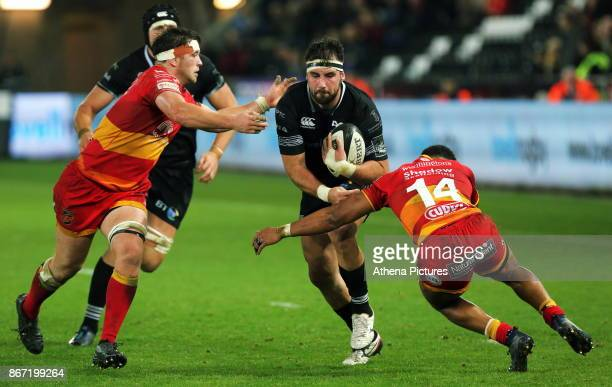 Scott Baldwin of the Ospreys is brought down by Ashton Hewitt of the Dragons during the Guinness PRO14 match between Ospreys and Dragons at The...
