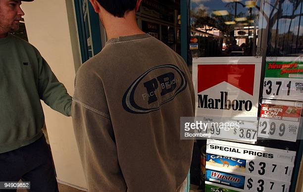 Scott Binley left and Dave Nolan walk past a sign advertising Marlboro brand cigarettes as they enter the Holy Smoke Tobacco shop in San Diego...