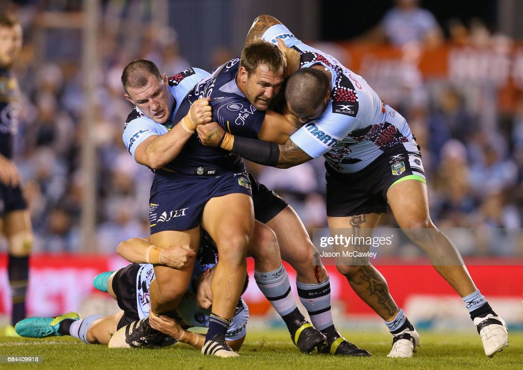 Scott Bolton of the Cowboys is tackled by Paul Gallen and Andrew Fifita of the Sharks during the round 11 NRL match between the Cronulla Sharks and the North Queensland Cowboys at Southern Cross Group Stadium on May 18, 2017 in Sydney, Australia.