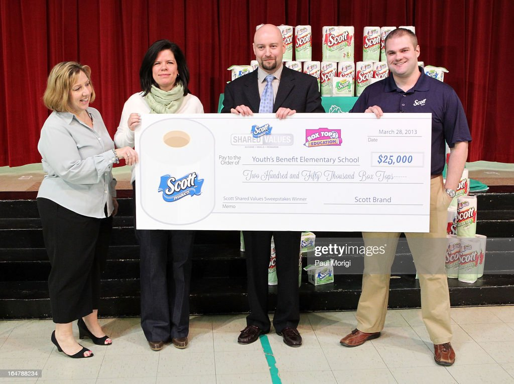 Scott Brand Manager Ben Johnson (R) presents a $25,000 check to (L to R) PTA President Laura Runyeon, Box Tops Coordinator Jenn Stump, and Principal Thomas Smith at a school assembly to celebrate the Scott Shared Values Sweepstakes award to Youth's Benefit Elementary School on March 28, 2013 in Fallston, Maryland.