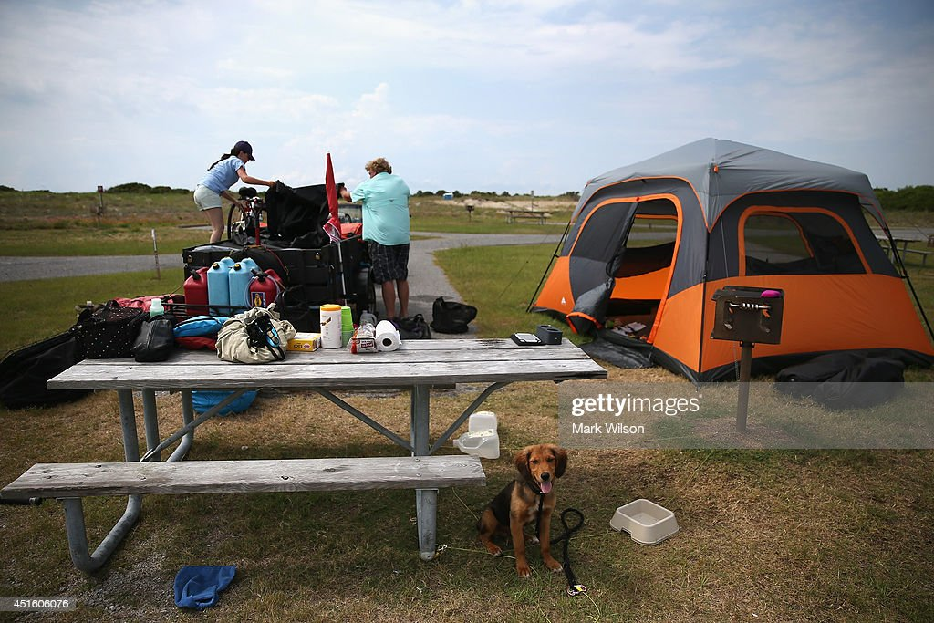 Scott Brooks (R) and Hannah Thomas (L) of Boston, MA break down their campsite while their dog sits nearby on July 2, 2014 in Oregon Inlet, North Carolina. Cape Hatteras National Seashore officials ordered all camp grounds to be evacuated by 12 noon today due to approaching tropical storm Arthur heading toward North Carolina's Outer Banks. Arthur has begun moving steadily northward at around 5 kt. and is expected to make landfall over the Fourth of July holiday.