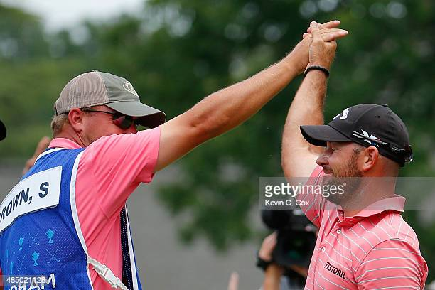 Scott Brown is congratulated by his caddie after scoring a holeinone on the third hole during the final round of the Wyndham Championship at...
