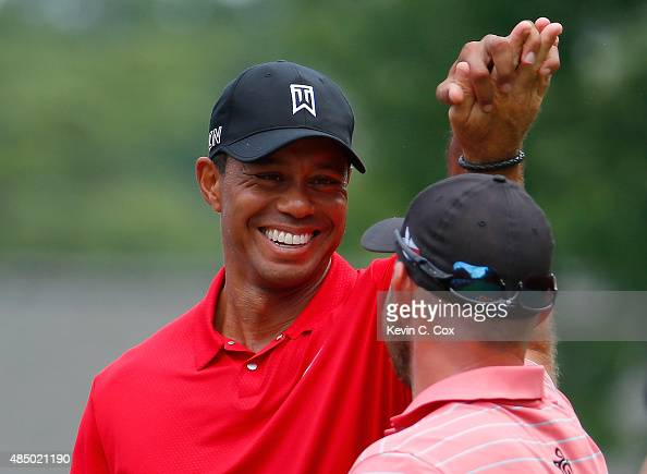 Scott Brown is congratulated by Tiger Woods after Brown scored a holeinone on the third hole during the final round of the Wyndham Championship at...