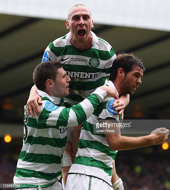 Scott Brown jumps on goal scorer Joe Ledley and Gary Hooper of Celtic during the Cooperative Insurance Cup final between at Hampden Park on March 20...