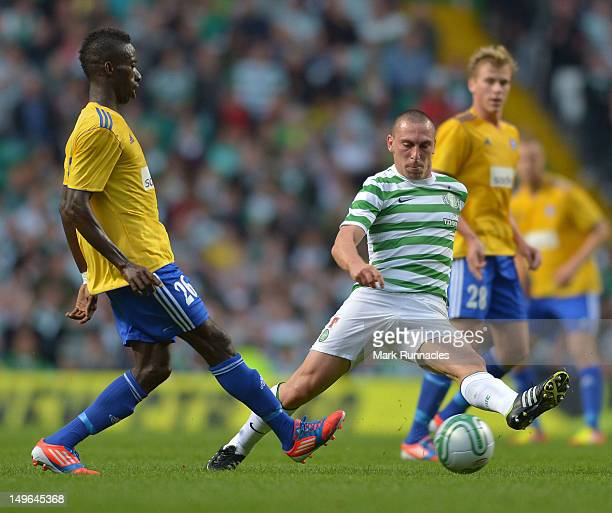 Scott Brown of Celtic challenges Demba Savage of HJK Helsinki during the Champions League thirdround qualifier first leg from Celtic Park on August 1...
