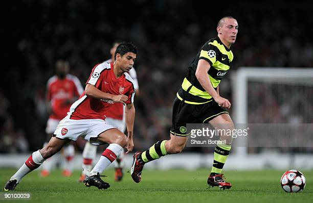 Scott Brown of Celtic is pursued by Eduardo of Arsenal during the UEFA Champions League 2nd qualifying round 2nd leg match between Arsenal and Celtic...