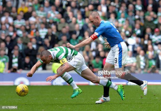 Scott Brown of Celtic is tackled by Kenny Miller of Rangers during the Ladbrokes Scottish Premiership match between Rangers FC and Celtic FC at Ibrox...
