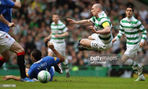 Scott Brown of Celtic is tackled by Kyle Bartley of Rangers during the Clydesdale Bank Premier League match between Celtic and Rangers at Celtic Park...
