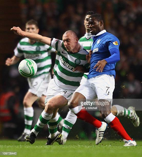 Scott Brown of Celtic is tackled by Maurice Edu of Rangers during the Scottish Cup fifth round match between Celtic and Rangers at Celtic Park on...