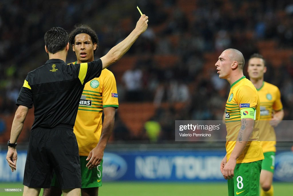 Scott Brown of Celtic receives a yellow card from referee Wolfgang Stark of Germany during the UEFA Champions League group H match between AC Milan and Celtic at Stadio Giuseppe Meazza on September 18, 2013 in Milan, Italy.