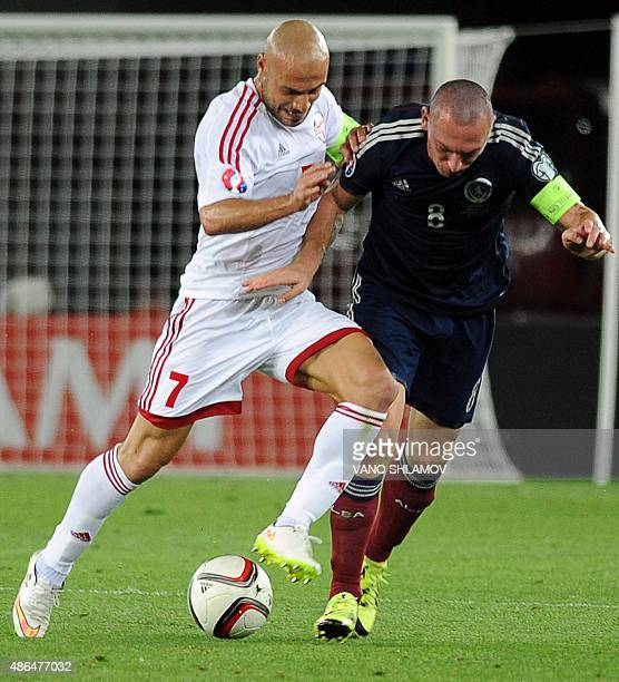 Scott Brown of Scotland vies for a ball with Jaba Kankava of Georgia during their Euro 2016 qualifying football match between Georgia and Scotland in...