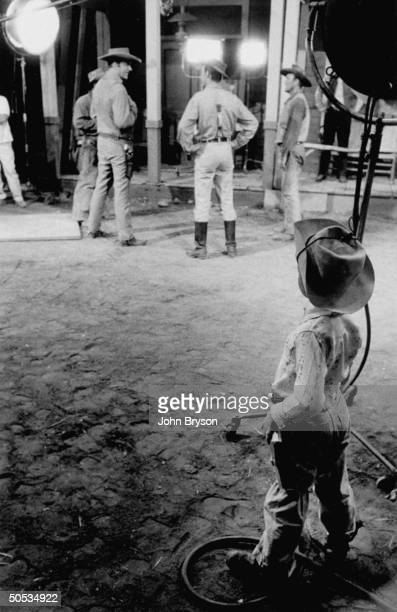 Scott Bryson son of photographer John Bryson dressed in cowboy outfit as he watches star James Arness in bkgrd during filming of Gunsmoke TV Western...