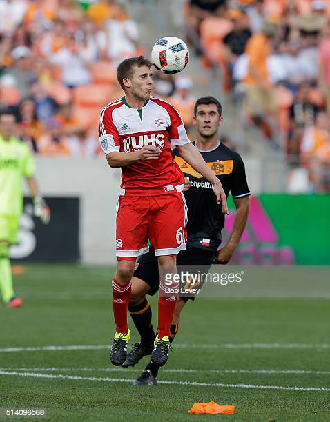 Scott Caldwell of New England Revolution heads the ball away from Will Bruin of Houston Dynamo at BBVA Compass Stadium on March 6 2016 in Houston...