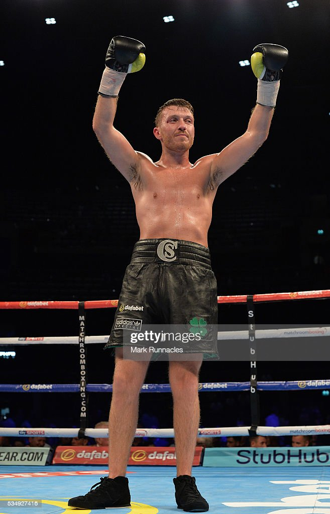 Scott Cardles (Black Shorts) celebrates his win over Ivan Njegac (Blue and White Shorts) during an undercard bout ahead of the WBA world super-lightweight title fight between Ricky Burns and Michele Di Rocco at The SSE Hydro on May 28, 2016 in Glasgow, Scotland.
