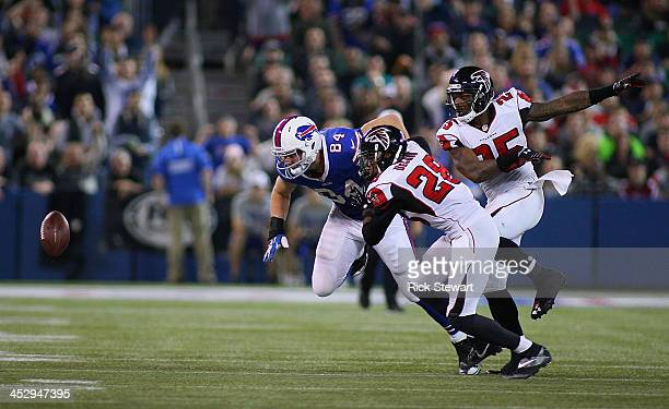 Scott Chandler of the Buffalo Bills fumbles in overtime against Thomas DeCoud and William Moore of the Atlanta Falcons at Rogers Centre on December 1...