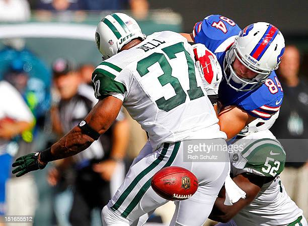 Scott Chandler of the Buffalo Bills has the ball knocked out of his hands by Yeremiah Bell and David Harris of the New York Jets during an NFL game...