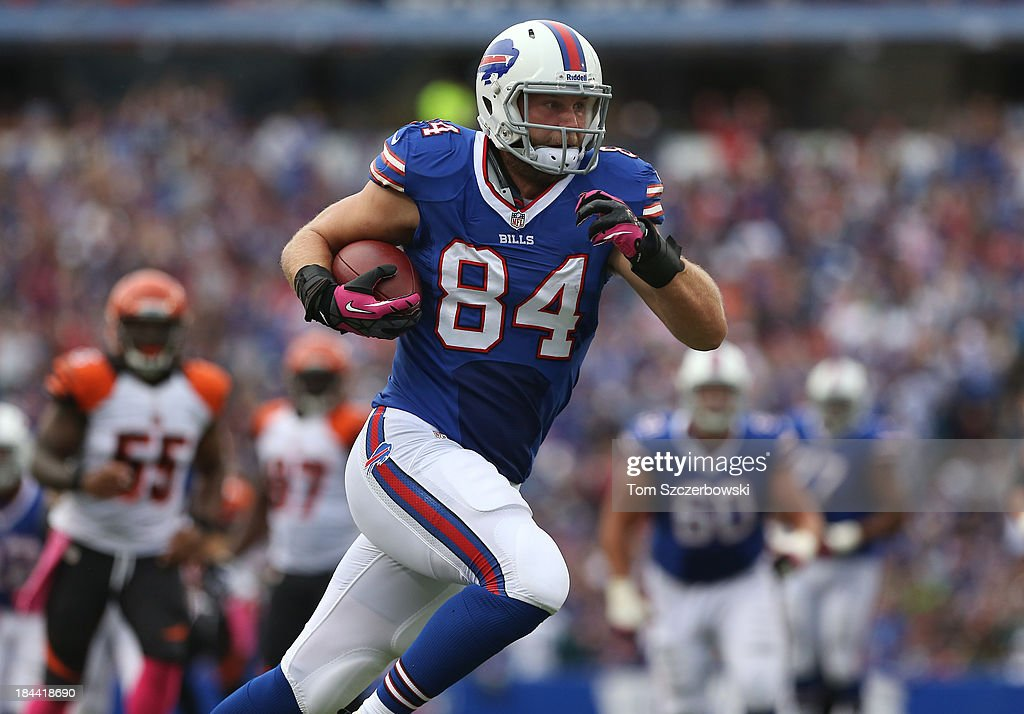 Scott Chandler #84 of the Buffalo Bills runs the ball in for a touchdown after making a reception during NFL game action against the Cincinnati Bengals at Ralph Wilson Stadium on October 13, 2013 in Orchard Park, New York.