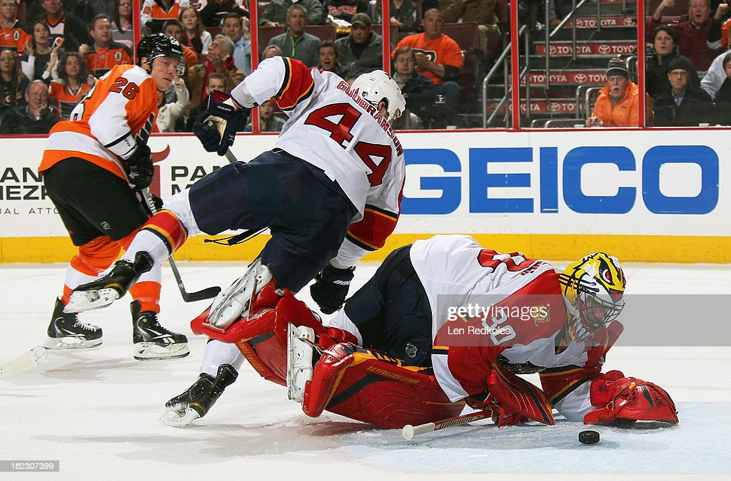 Scott Clemmensen #30 of the Florida Panthers keeps his eyes on the puck while teammate Erik Gudbranson #44 loses his balance and Ruslan Fedotenko #26 of the Philadelphia Flyers looks for a rebound on February 21, 2013 at the Wells Fargo Center in Philadelphia, Pennsylvania.