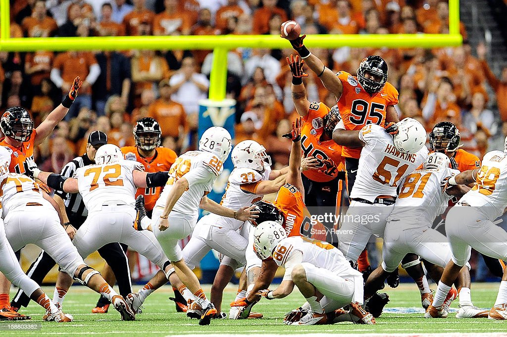 Scott Crichton #95 of the Oregon State Beavers blocks a field goal attempt by Nick Jordan #28 of the University of Texas Longhorns during the Valero Alamo Bowl at the Alamodome on December 29, 2012 in San Antonio, Texas.
