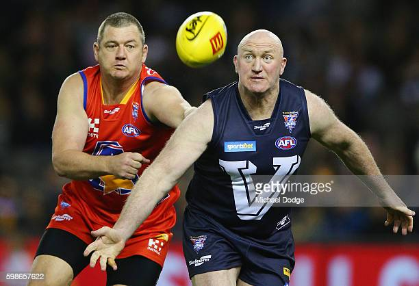 Scott Cummings of the All Stars and Mick Martyn of Victoria compete for the ball during the EJ Whitten Legends match at Etihad Stadium on September 2...