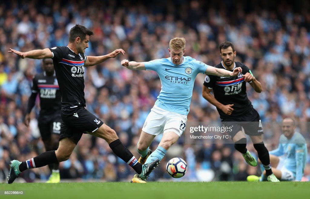 Scott Dann of Crystal Palace attempts to tackle Kevin De Bruyne of Manchester City during the Premier League match between Manchester City and Crystal Palace at Etihad Stadium on September 23, 2017 in Manchester, England.