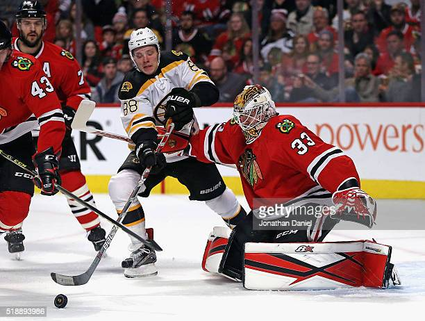 Scott Darling of the Chicago Blackhawks holds off David Pastrnak of the Boston Bruins as he tries for the puck at the United Center on April 3 2016...
