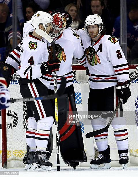 Scott Darling of the Chicago Blackhawks is congratulated by teammates Niklas Hjalmarsson and Duncan Keith after the game against the New York Rangers...