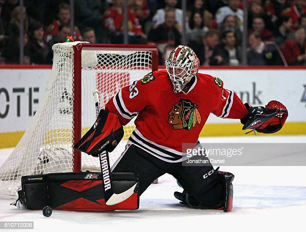 Scott Darling of the Chicago Blackhawks knocks the puck away for a save against the Toronto Maple Leafs at the United Center on February 15 2016 in...