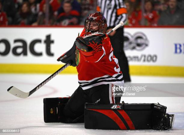 Scott Darling of the Chicago Blackhawks reaches for the puck against the Colorado Avalanche at the United Center on March 19 2017 in Chicago Illinois...