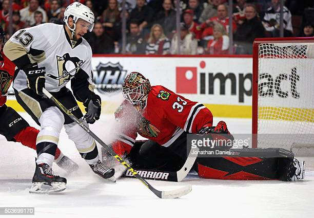 Scott Darling of the Chicago Blackhawks sprawls to make a save against Nick Bonino of the Pittsburgh Penguins at the United Center on January 6 2016...