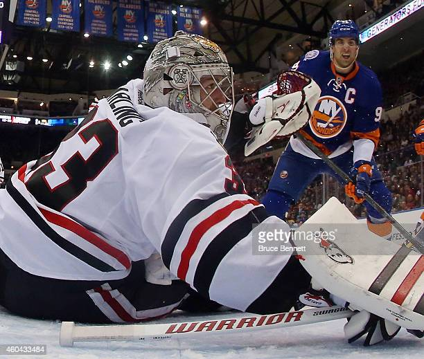 Scott Darling of the Chicago Blackhawks tends net against John Tavares of the New York Islanders at the Nassau Veterans Memorial Coliseum on December...