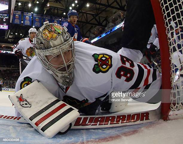 Scott Darling of the Chicago Blackhawks tends net against the New York Islanders at the Nassau Veterans Memorial Coliseum on December 13 2014 in...