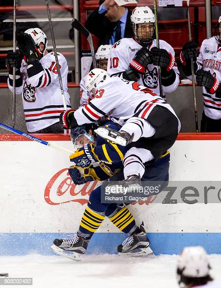 Scott Davidson of the Quinnipiac University Bobcats checks Colton Saucerman of the Northeastern Huskies over the boards at the Northeastern bench...