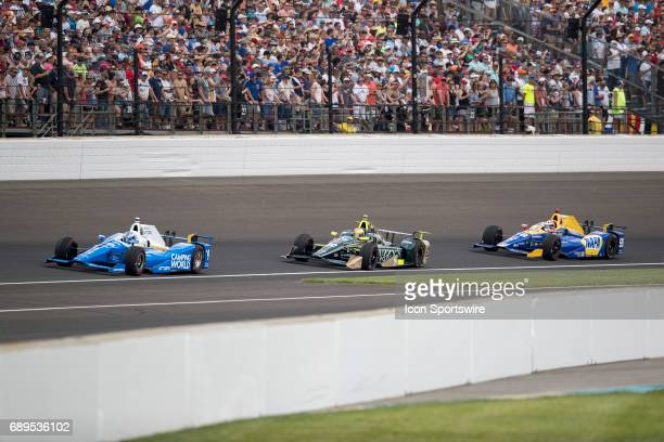 Scott Dixon driver of the Chip Ganassi Racing Honda leads Ed Carpenter driver of the Ed Carpenter Racing Chevrolet and Alexander Rossi driver of the...