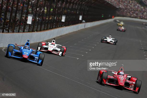 Scott Dixon driver of the Target Chip Ganassi Racing Chevrolet Dallara fights for the lead with Tony Kanaan of Brazil driver of the NTT Data Chip...