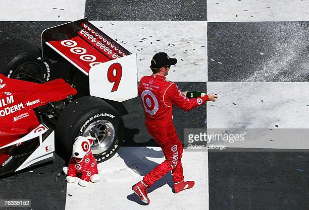 Scott Dixon driver of the Target Chip Ganassi Racing Dallara Honda sprays champagne in celebration in victory circle after winning the IRL Indycar...